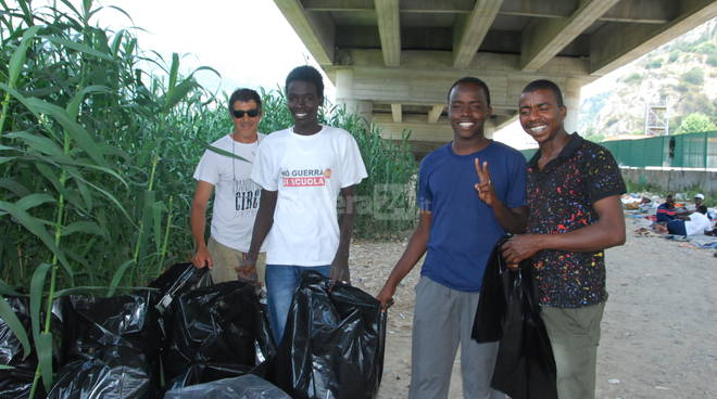 Migranti pulizia fiume Roja,